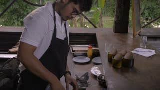 A chef prepares bread with oil and salt and then puts it on the grill in a semi-outdoor environment or restaurant.
