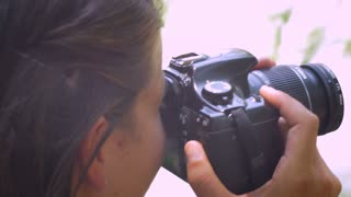 A close up shot of a young attractive 20 something women takes photos of nature and city while traveling with a dslr camera. Hand held and over the shoulder.