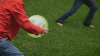 A couple of young boys play balloons outside in a park with their mother in slowmo