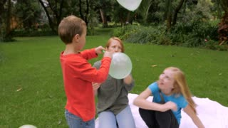 A couple of young kids start hitting a balloon around with their family outside in a park - slowmo