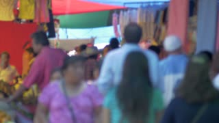 A crowded outdoor market in a latino country busy with shoppers walking by the camera out of focus.