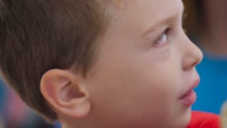 A cute, young, little boy looking around smiling slightly - slow motion closeup
