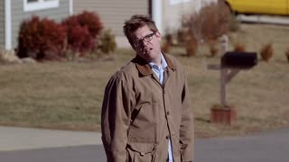 A depressed man walks away in suburbia looking disheveled and unkempt.