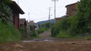 A dirt road in rural Mexico with newer nice homes and electric wires shot from the ground - dolly shot