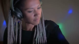 A DJ wearing wireless headphones working and mixing music in a club in slow motion