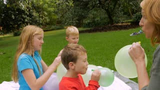 A family blowing up balloons lets them go as they fly away showing pure joy and excitement- slowmo steadicam