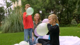 A family including a redheaded mother, two young sons, and a blond haired prepubescent girl let their balloons fly away and one hits the camera - slowmo