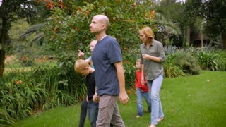A family of 5 exploring a tropical garden together while holding hands - slowmo steadicam