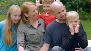 A family of 5 make funny faces together for a portrait outside in slow motion including two young brothers and their older sister.