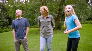 A family of 5 standing around in the grass barefoot - slowmo steadicam
