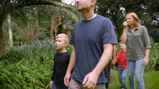A family of five walk through a park looking at and smelling plants - slowmo steadicam.