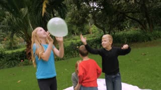 A family of four starts a simple game of hitting balloons in the air at a park - slowmo steadicam