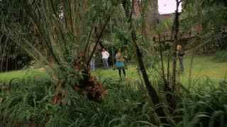 A family playing in a park and on a swing - wide shot, slowmo, steadicam
