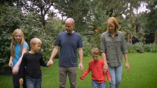 A father, mother, young daughter, and two young sons walking barefoot through the grass while holding hands together - slow motion steadicam