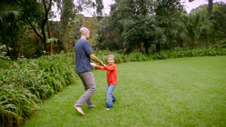 A father spins his 5 year old son around in circles on the grass - slowmo steadicam