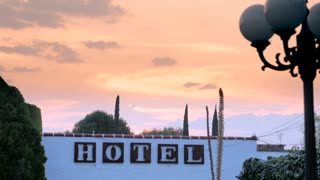 A generic hotel sign against a sunrise or sunset while a bird flies by against the sky - dolly shot.