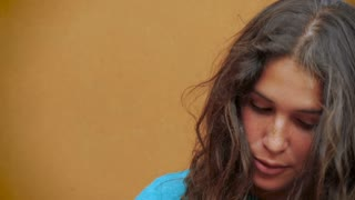 A genuine moment with an attractive young woman smiling with curly long hair in slow motion