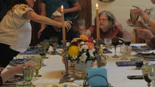 A group of friends and family pour champagne at dinner party or passover seder celebration.