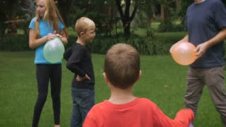 A group of kids play with their father in a park with balloons - slowmo steadicam