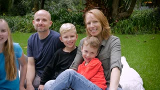 A happy family of 5 sitting outside during the summer or spring, smile for the camera - dolly shot