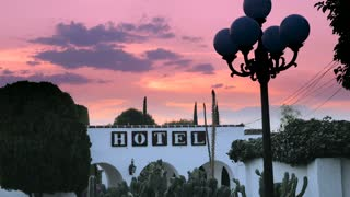 A hotel sign on a white arched wall against a dramatic sunset or sunrise with cactus plants and an old lamppost dolly shot