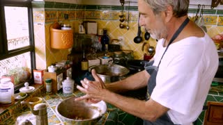 A Jewish baby boomer has fun making homemade matzah balls or meat balls for a family dinner in a modern kitchen.