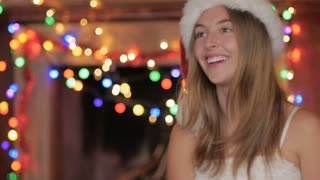 A jolly happy attractive blond woman wearing a red Santa hat laughing in the holiday spirit with Christmas lights decorating the fireplace mantel behind her.