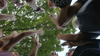 A large group of people high five together in a circle from multiple generations - shot from below