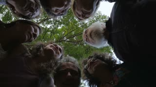 A large group of people huddle together in unison shot from below to celebrate something