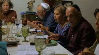A large group of seniors eating at a dinner party or passover seder