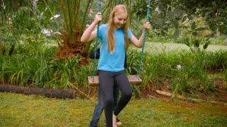 A little blond haired boy pushes a young girl on a swing in a park - slowmo.