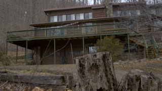A log home in the woods in the winter with trees without leaves and a rotting stump in the foreground during the day - establishing dolly shot