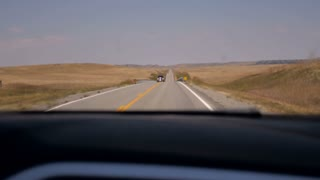 A lone truck approaches the camera while driving on a two lane rural road in central Montana.