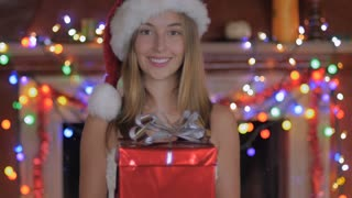A lovely young woman giving a wrapped Christmas gift and smiling with colored lights hanging in the background