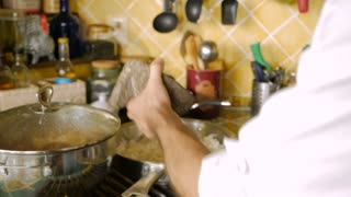 A man adds ground pepper from a mortar and pestle to a pan of grilled onions and covers them in slow motion