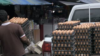 A man carries crates of eggs from the back of his pickup truck into a market while wearing flip flops