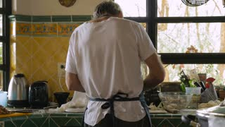 A man chops food in his kitchen shot from behind