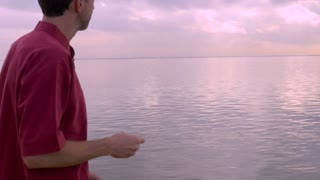 A man in a red shirt is skipping stones in the calm water on a beach during sunrise or sunset.