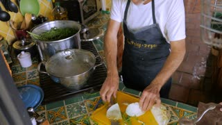 A man in his 60s puts cut cabbage into a large pot of soup with herbs - high angle