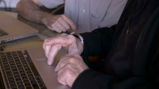A man points to a computer while an elderly senior man uses the trackpad on his laptop. The younger man could be his son, or teacher.