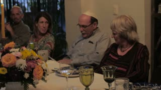 A man reads from a book (Haggadah) at a dinner table during a passover seder