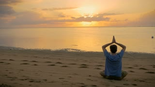 A man sitting in a lotus yoga pose lowers his arms and puts his arms out to the side during a magnificent, breathtaking, impressive sunrise or sunset