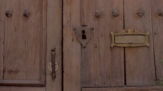 A man unlocks a beautiful old wooden door and enters his home approaching steps and a garden in slow motion, feeling like he is welcomed into his luxurious colonial home.