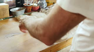 A man uses a rolling pin on a wooden cutting board in his home kitchen or restaurant - hand held shot from behind