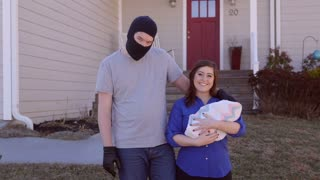 A man wearing a ski mask has his arm around a woman with a baby