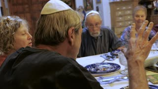 A man wearing a yarmulke leads a toast at a large dinner table such as a passover seder or jewish cultural event - handheld