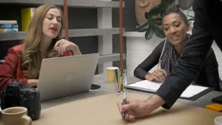 A man writes an idea on paper with his female co workers at a strategy meeting in a casual office environment.