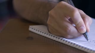 A man writes in a spiral bound paper notebook with a pen - dolly shot close up