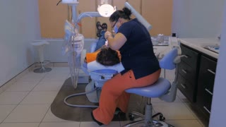 A Mexican dentist works on a dental patient showing her modern dental clinic in Mexico - wide dolly from behind