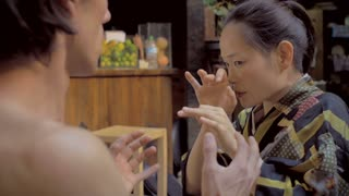 A Mexican man has an attact of DTs at a bar or restaurant next to his Japanese girlfriend during a butoh dance performance.
